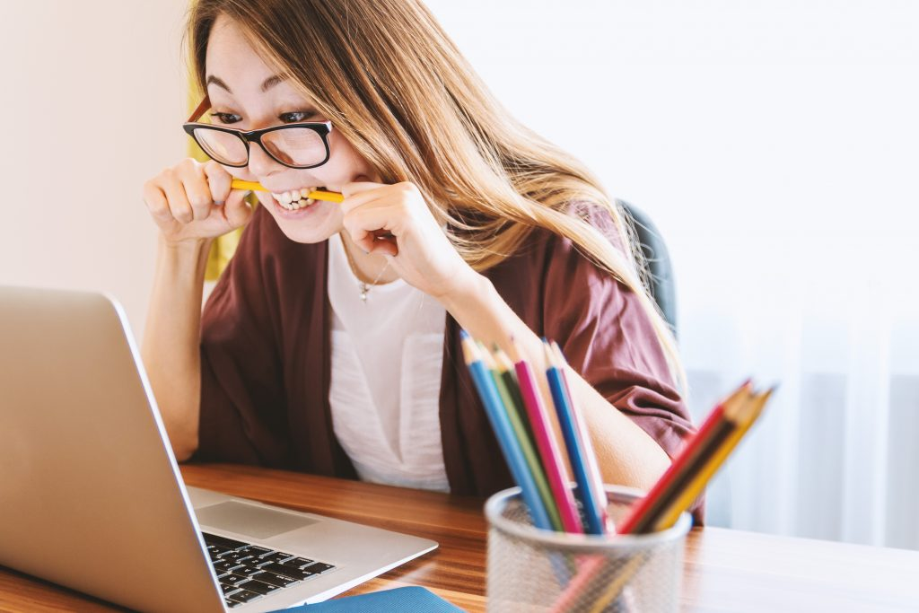 woman biting pencil in front of computer