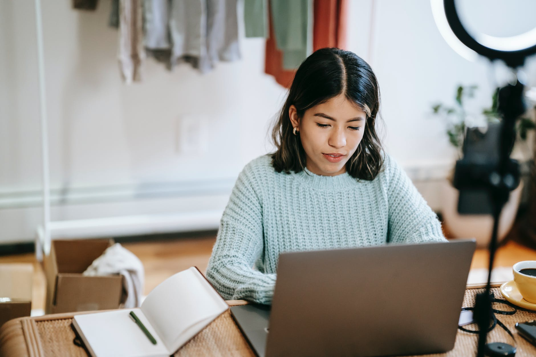 hispanic lady working remotely on laptop near notebook in room